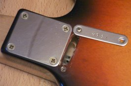Serial number plate of 1977 Custom Masquerader removed to show truss rod adjuster slot and pierced adjustment nut
